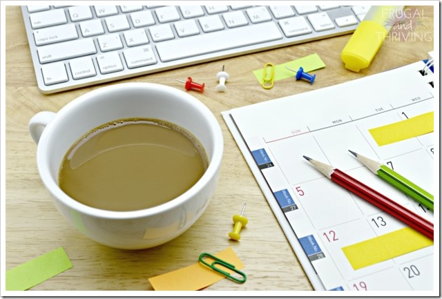 Coffee cup, diary, sticky notes, pencil, pin, clip and keyboard on wooden table