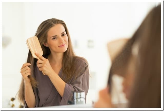 Young woman combing hair in bathroom