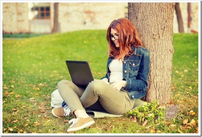 smiling teenager in eyeglasses with laptop