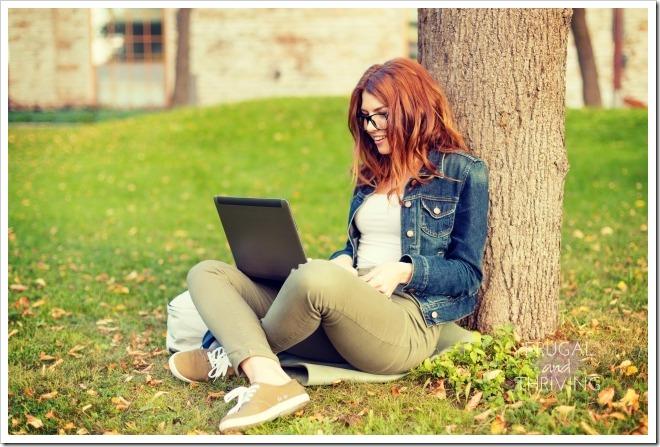 smiling teenager in eyeglasses with laptop
