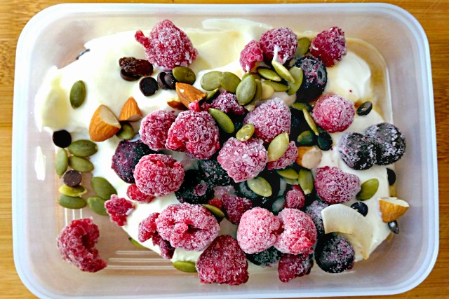 yoghurt topped with frozen berries and trail mix