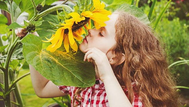 girl enjoying the simple pleasures of smelling the flowers