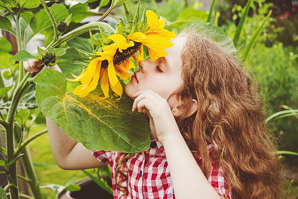 girl enjoying simple pleasures of smelling flowers