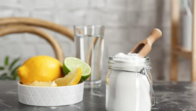 jar of bicarb soda with lemons and limes representing uses for bicarb soda